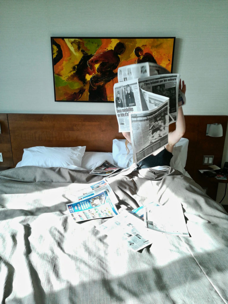 Alice playing with the newspaper in bed at Hotel Chateau Laurier in Québec