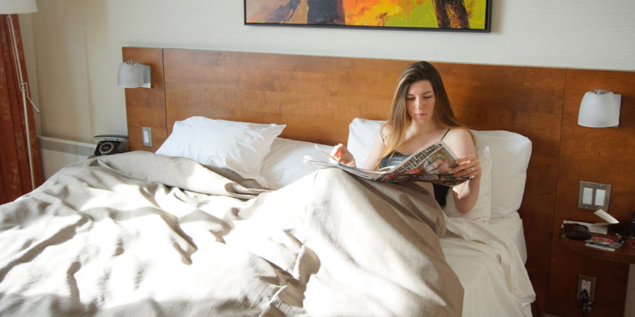 Alice reading the news in bed in the Luxueuse room in Hôtel Château Laurier in Québec city