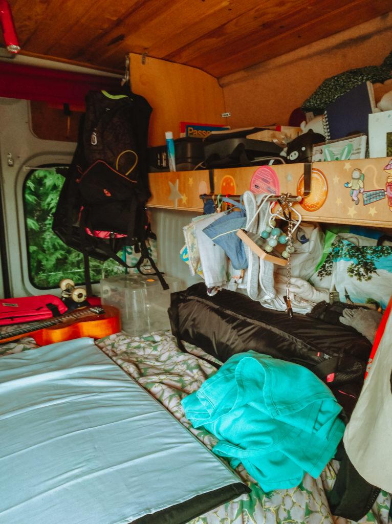 couchage et rangements dans un van aménagé pour voyager avec un bébé