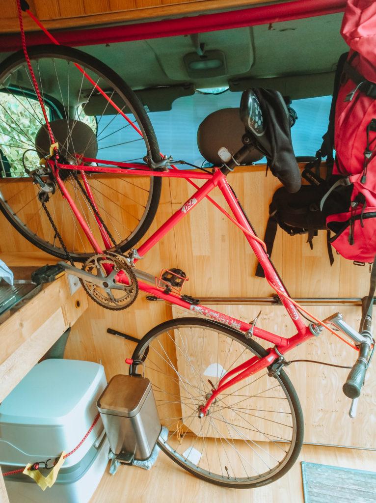vélo accroché à l'intérieur d'un van aménagé pour voyager avec un bébé