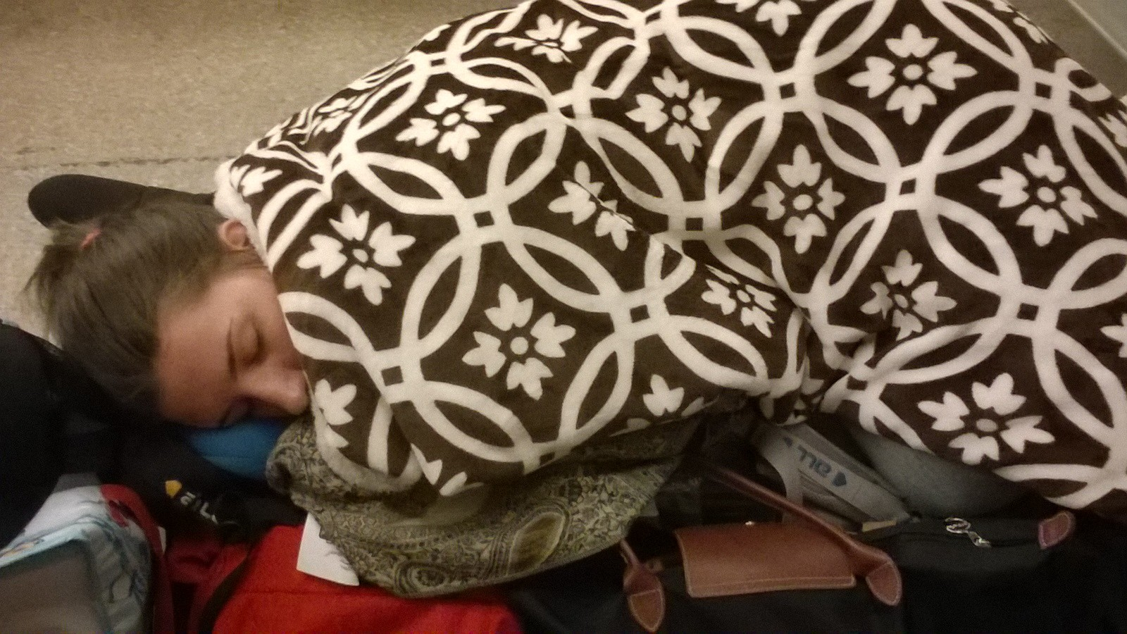 Alice sleeping on our backpacks at Savannah Greyhound station