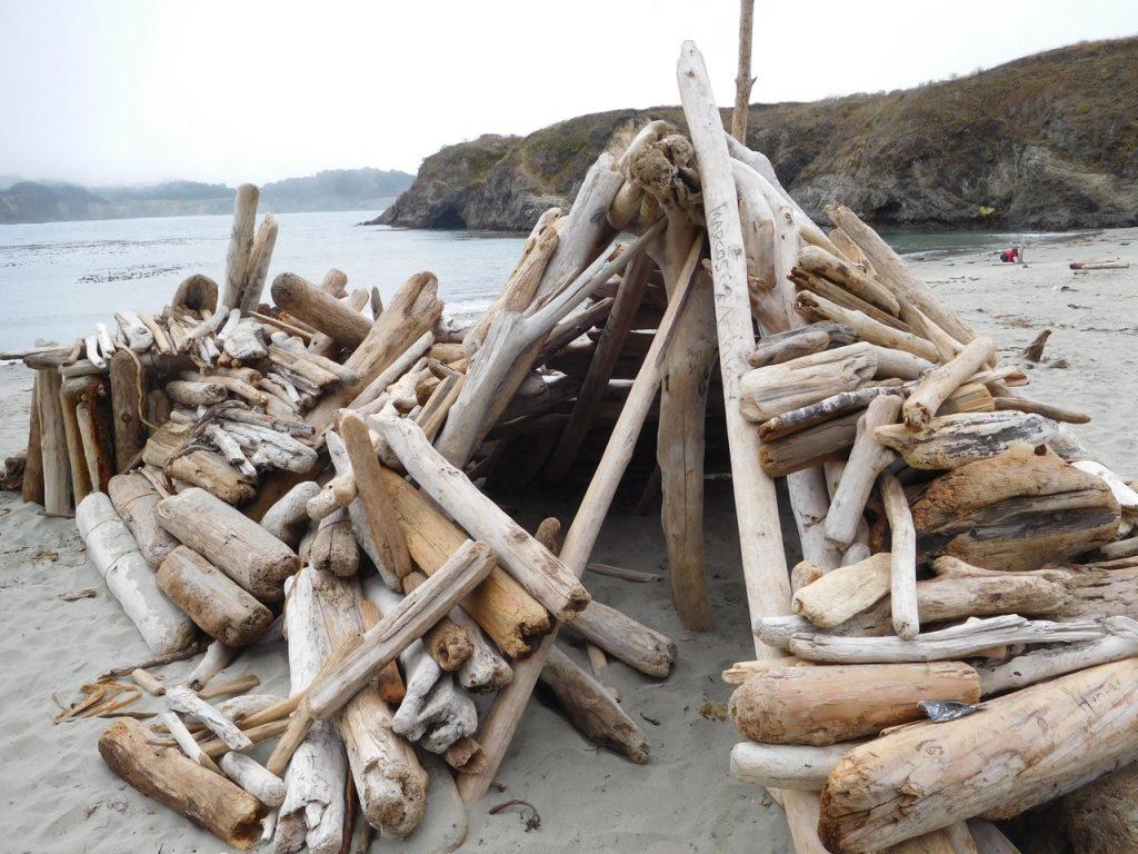wood teppees on the beach