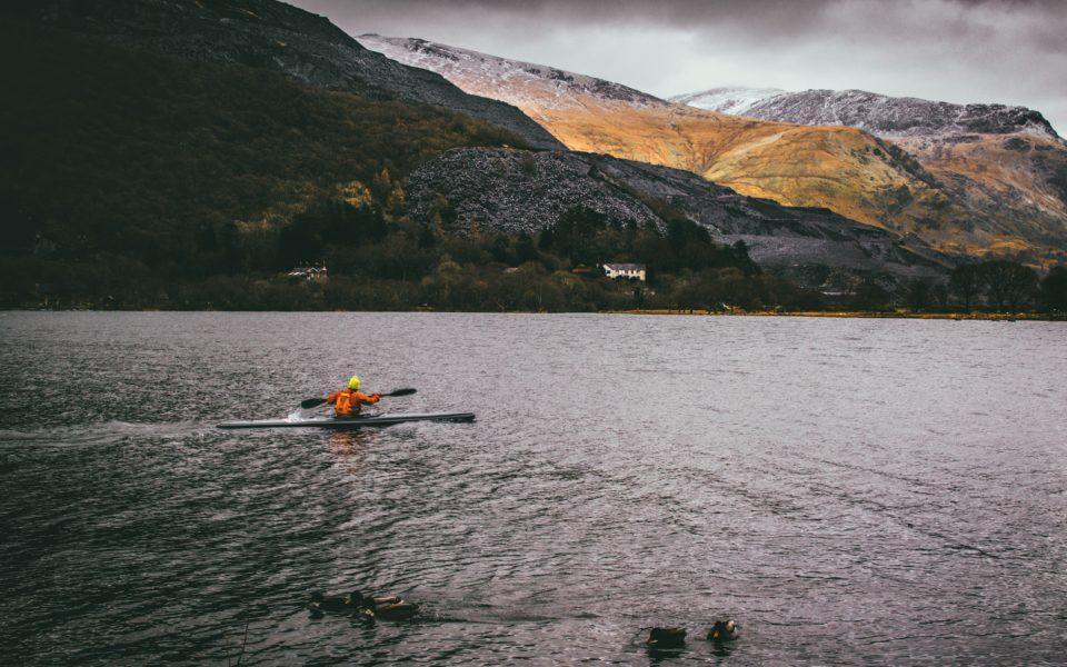 Homme en train de faire du canoe au milieu des montagnes