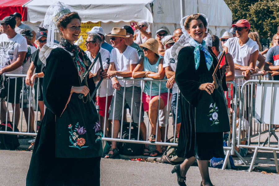 Women wearing traditional outfits walking the Grand Parade at the Inter-Celtic Festival in Lorient