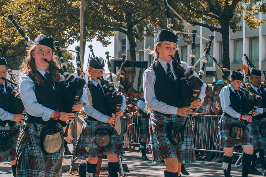 Young women from Ireland playing the bagpipes during the Grand Parade at the Inter-Celtic Festival in Lorient
