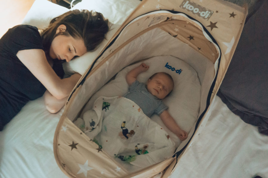 Alice and baby sleeping in the Koo-di travel bassinet