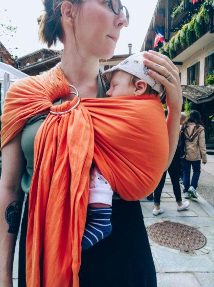 Maman portant son bébé en sling à la montagne